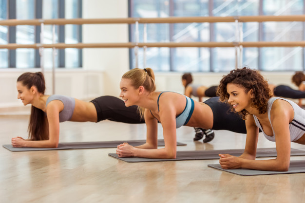 three-attractive-sport-girls-smiling-while-doing-plank_85574-6138